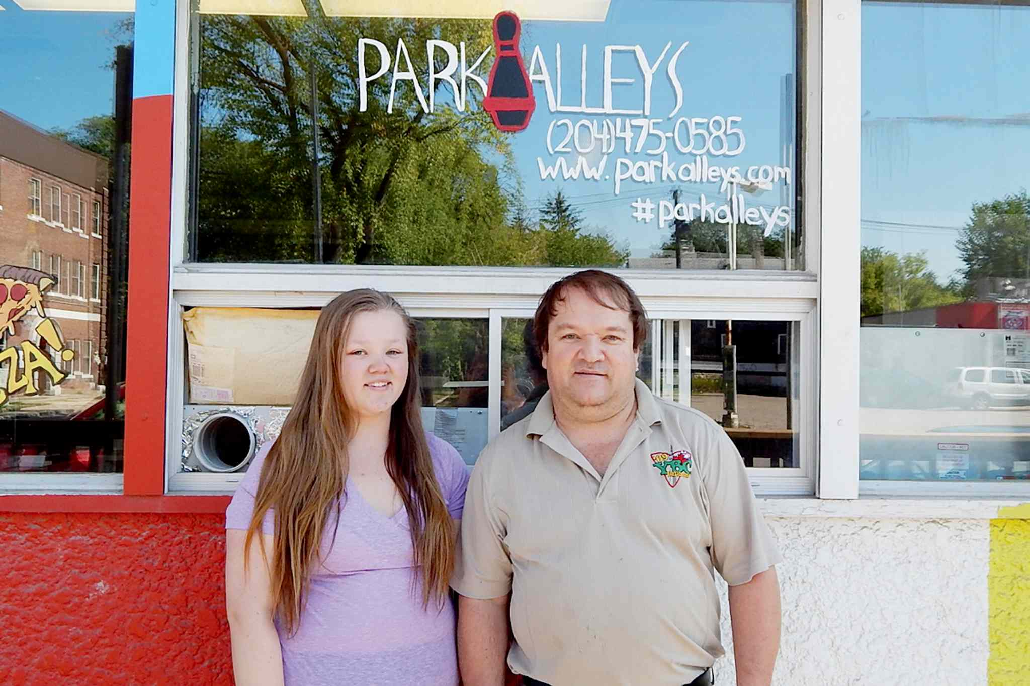 Park Alleys owner Mike Devenney, right, stands with his daughter Jennifer outside the newly-renovated Park Alleys bowling centre at 730 Osborne St.