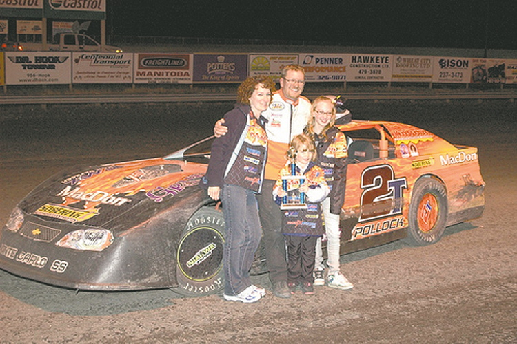 Derek Pollock and his family pose in front of one of his racing cars.