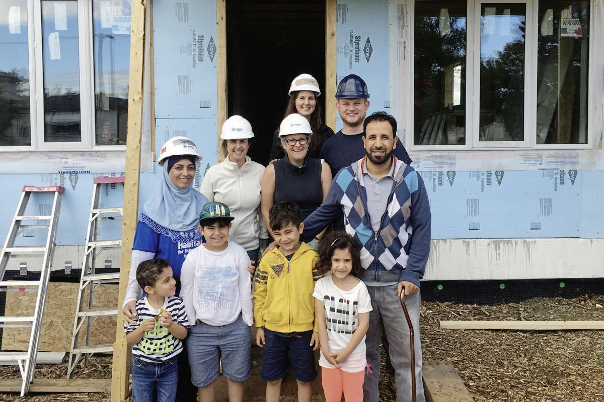 Giti and Ahmad, and their four children, with Elmwood-Transcona MP Daniel Blaikie and staff volunteering on a Habitat for Humanity Project in the constituency.