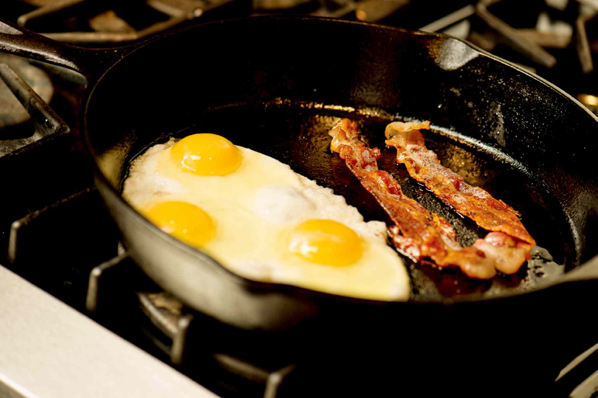 To get stubborn grease out of an old cast iron frying pan, try washing with dish soap and water, and wiping the inside and outside with some vegetable oil and a paper towel.