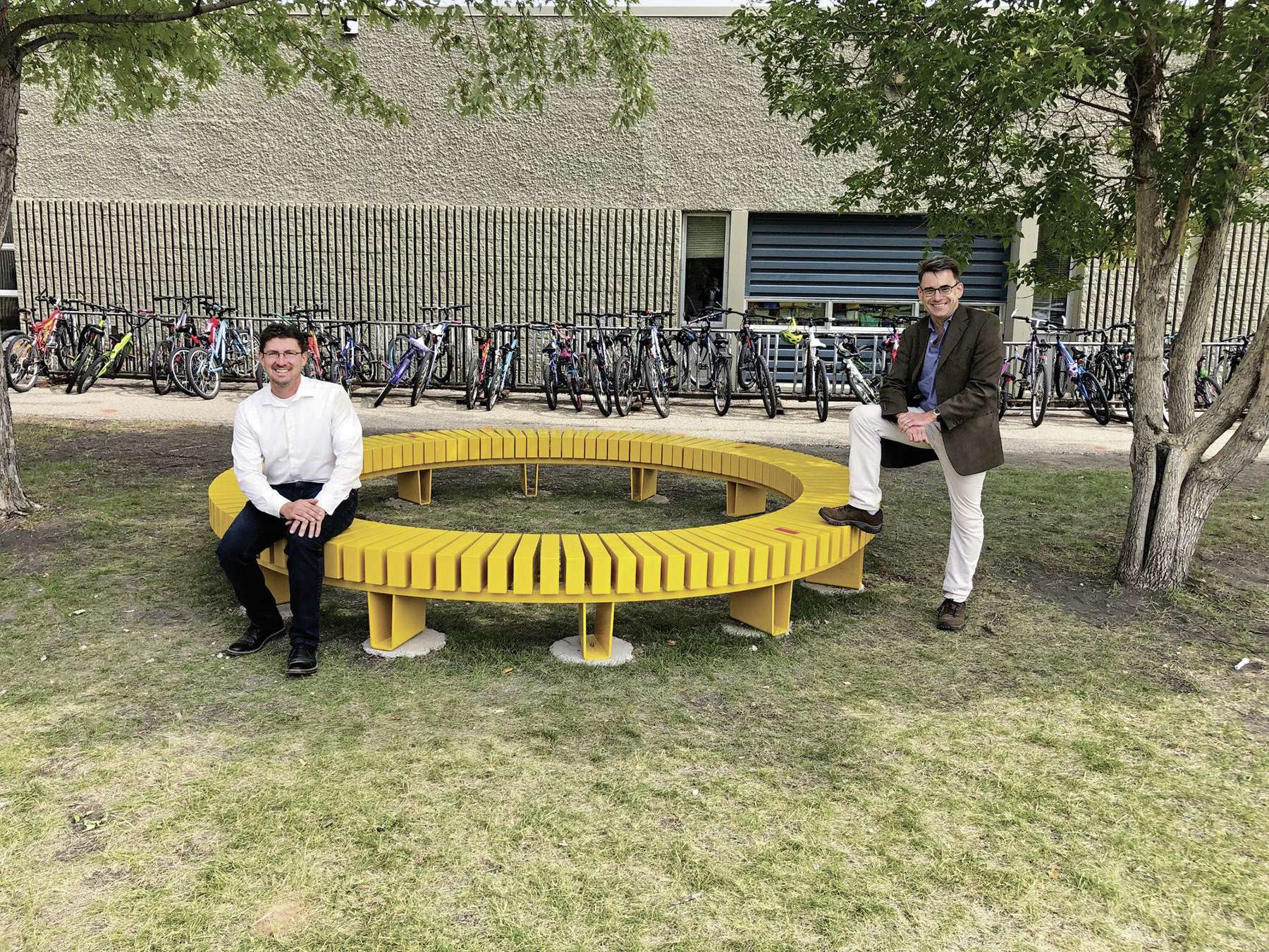 City councillors Matt Allard (St. Boniface, at left) and Brian Mayes show off the new circular bench at École Guyot that they funded.