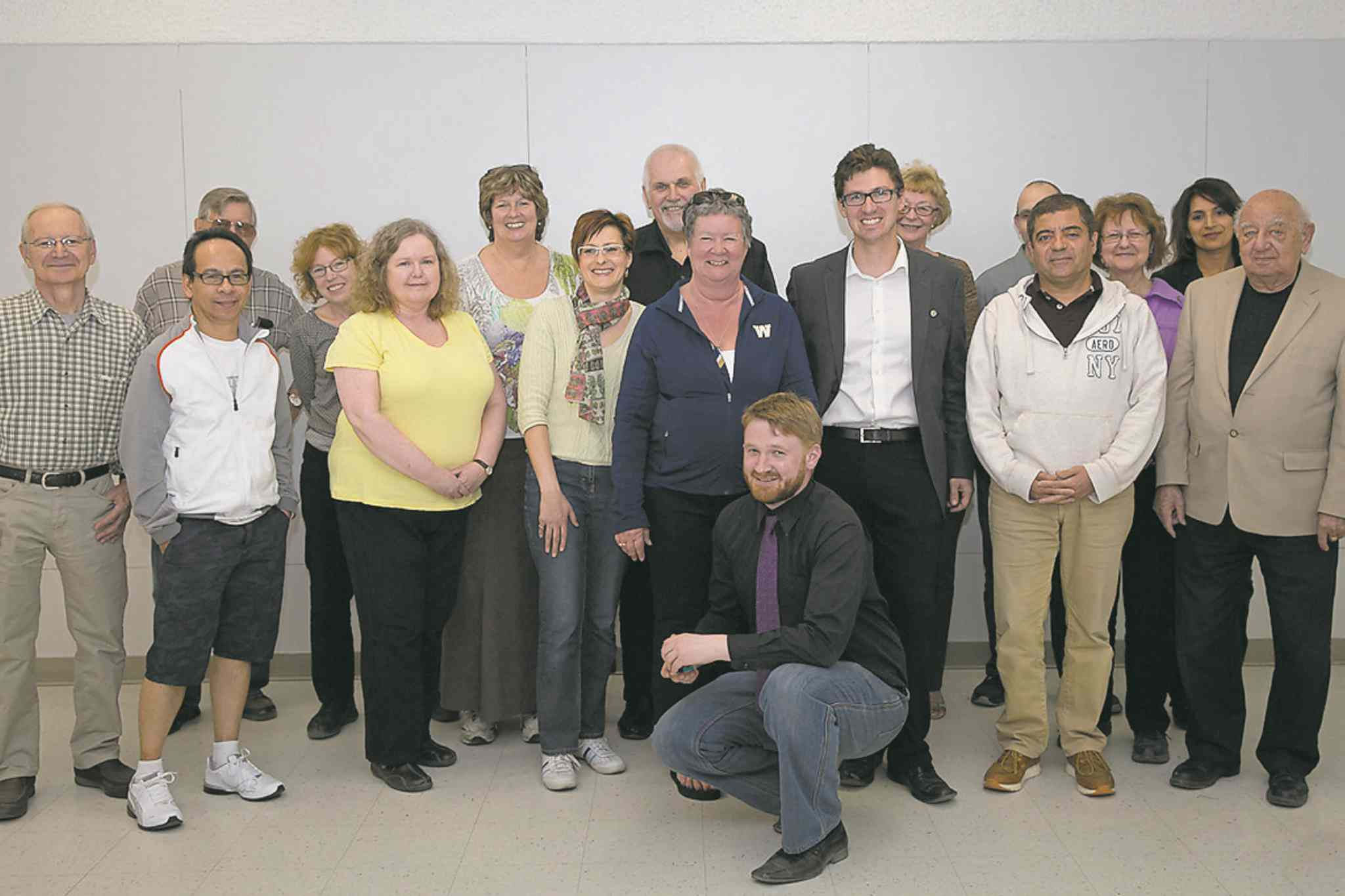 Matt Allard (centre) and executive assistant Ryan Palmquist (kneeling) are pictured with Royalwood residents at a town hall meeting on April 14.
