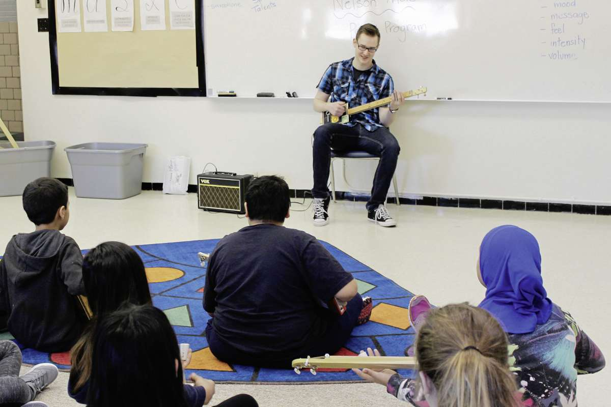 J.H. Bruns student Connor Rose demonstrates his skills on a cigar box guitar to students at Marion School. Rose personally built enough of the guitars for each of the 22 students to have for the class, and keep afterward.