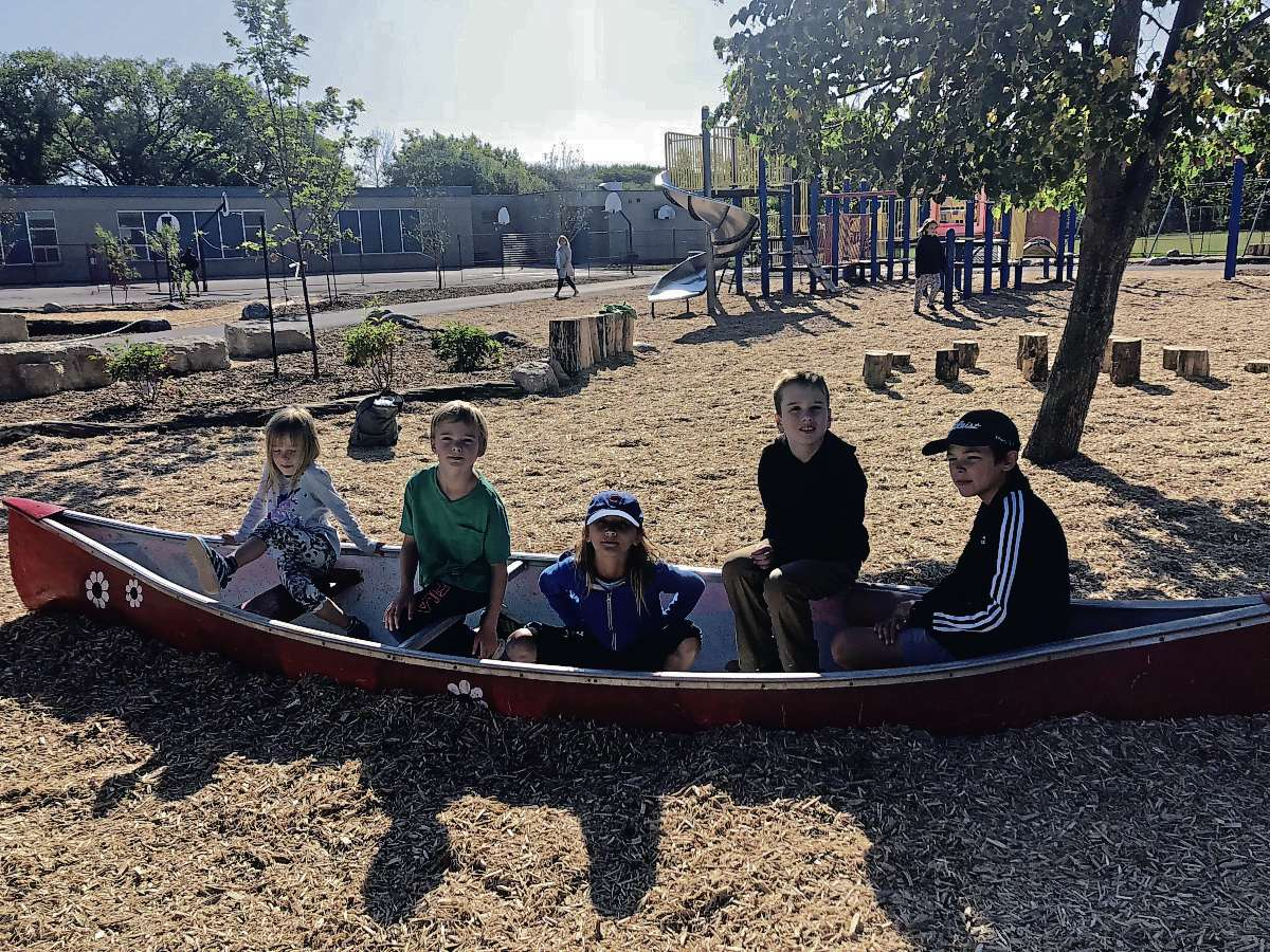From left: Nordale School students Lily, Liam, Evy, Owe and Emerson test one of two canoes that are part of the school's new nature playground.
