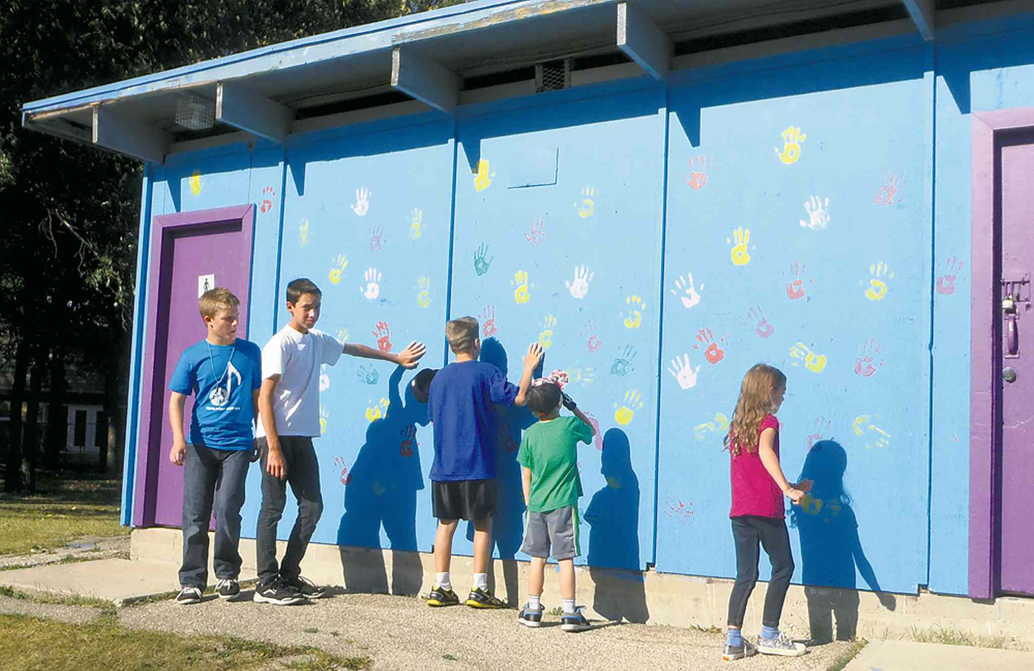 Westwood kids check out the handprints and images now decorating the changing room building at John Steel Park.