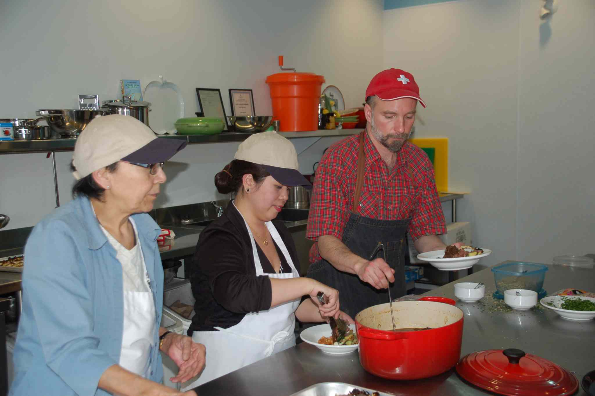 Community volunteers (left to right) Sharon Czuba, Abby Legaspi and Grant Mitchell serve a lunch of beef, beans, rice pilaf and zucchini at the official opening of the NorWest Co-op Community Food Centre on March 13.