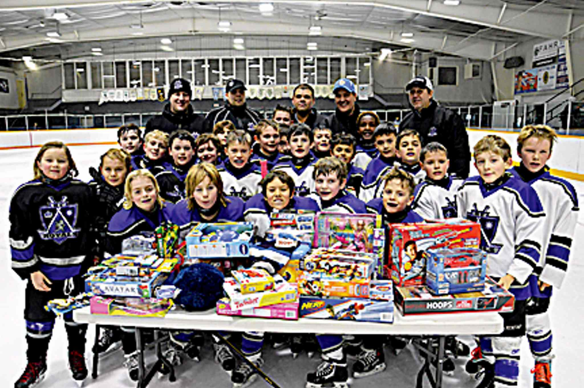 The Royals 9A1 White and Black hockey teams and their coaches pose with toys they collected for the Christmas Cheer Board.