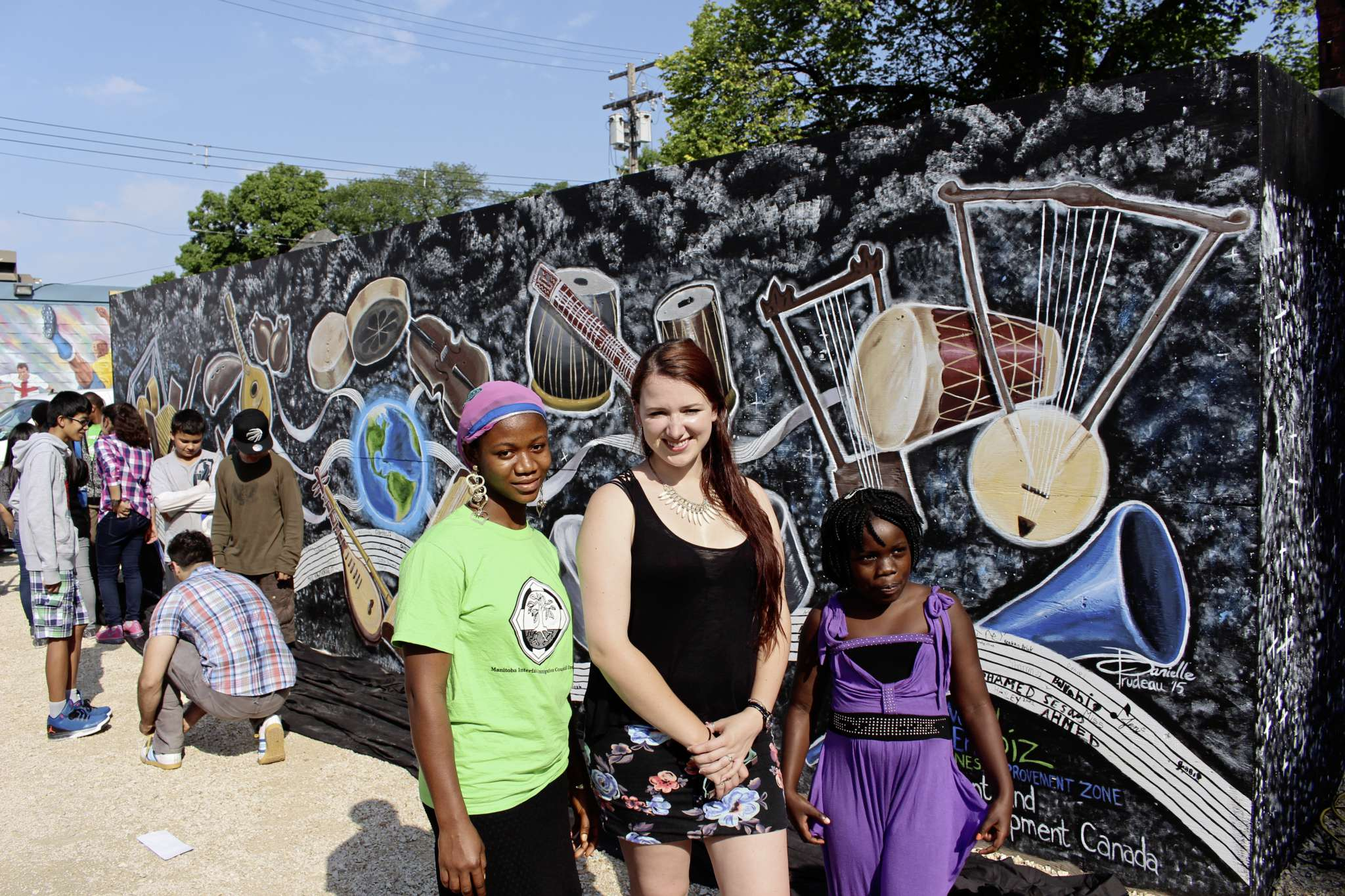 From l-r: Mayongbe Jabati, Danielle Trudeau and Sharon Gatoro stand in front of the new mural at the corner of Sargent Avenue and McMicken Street.