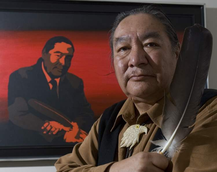 Former politician and honourary Cree Chief Elijah Harper holds up one of two eagle feathers he held during the Meech Lake proceedings. (Tom Hanson / THE CANADIAN PRESS Archives)
