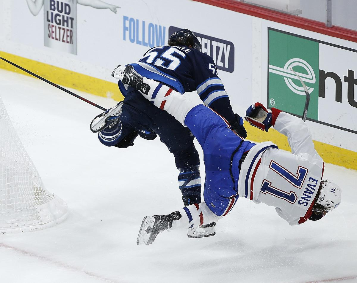 Winnipeg Jets' Mark Scheifele hits Montreal Canadiens' Jake Evans after he scored an empty net goal during third period NHL Stanley Cup hockey action June 2.