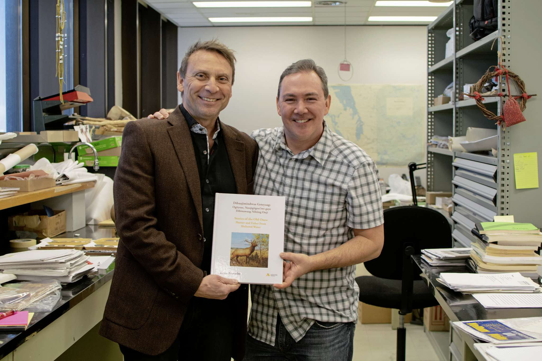 Manitoba Museum's curator of archeology Kevin Brownlee (right) and designer Ed Winters hold a copy of Brownlee's new book, Stories of the Old Ones: Hunter and Fisher from  Sheltered Water.