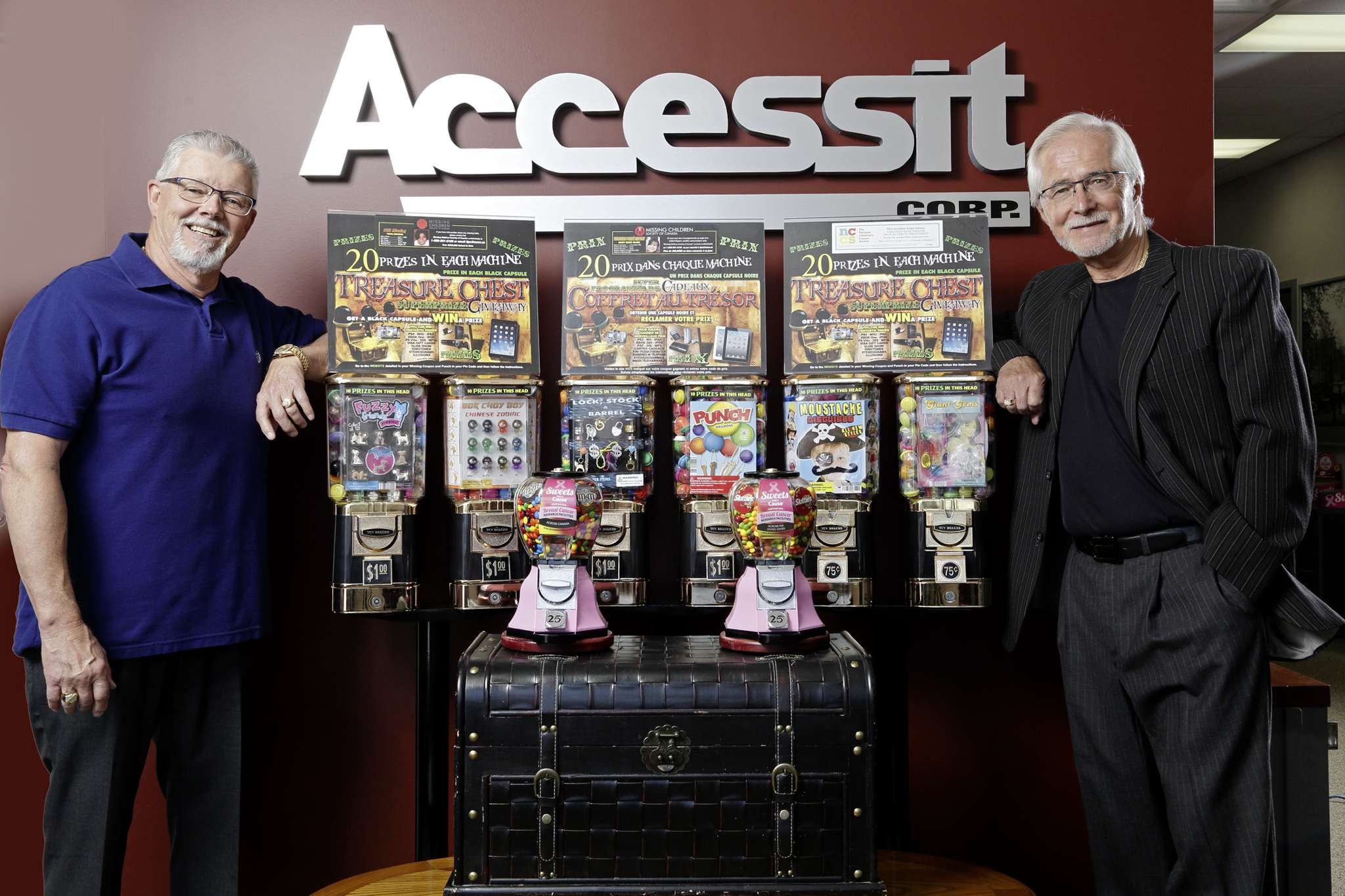 Accessit Corp. president Paul Shepperson and chief executive officer Tom Semeniuk stand with their vending machines for charity.