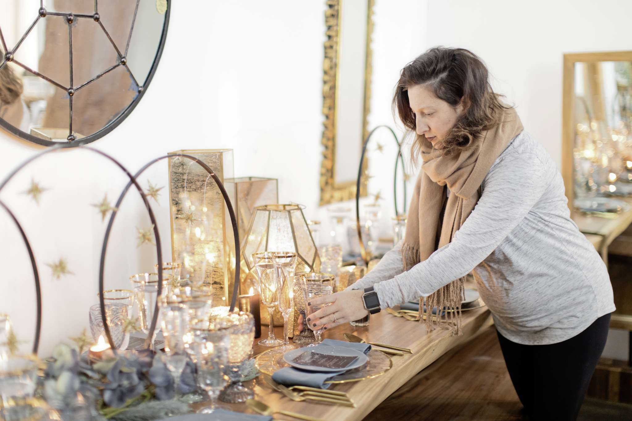 "Designer Sacha Jammu of French Accent Design puts the finishing touches on her ""Starry Night"" tablescape set atop a live edge table at Blue Moon Furniture."