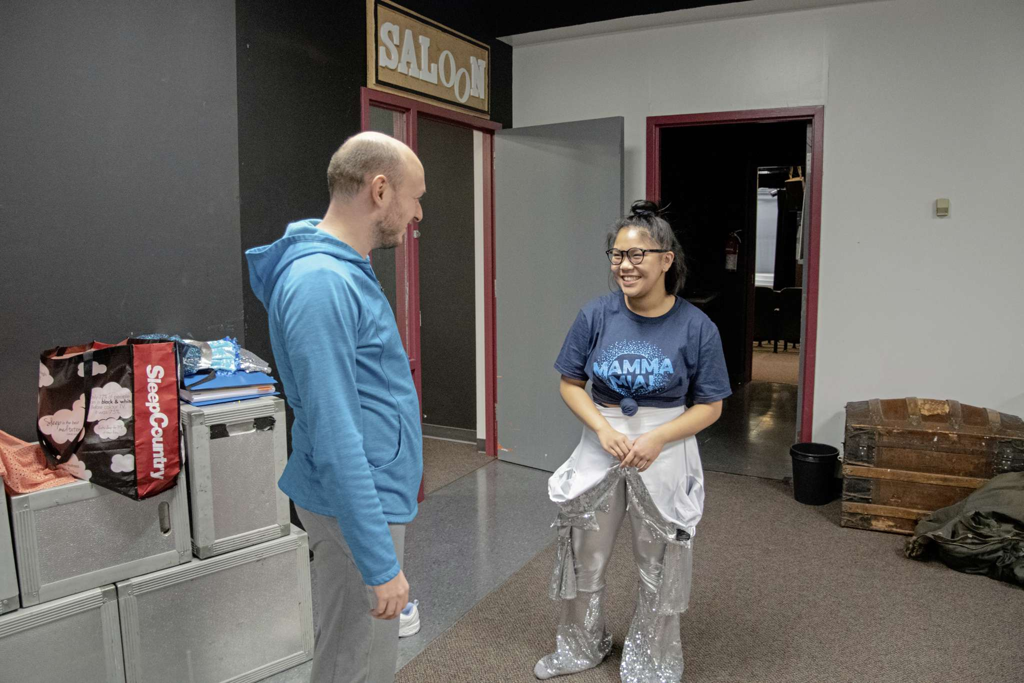 Westwood Collegiate student Charlize Tan (right) chats with Mamma Mia! co-director Brian Toms while she tries on a costume for the productions final number.