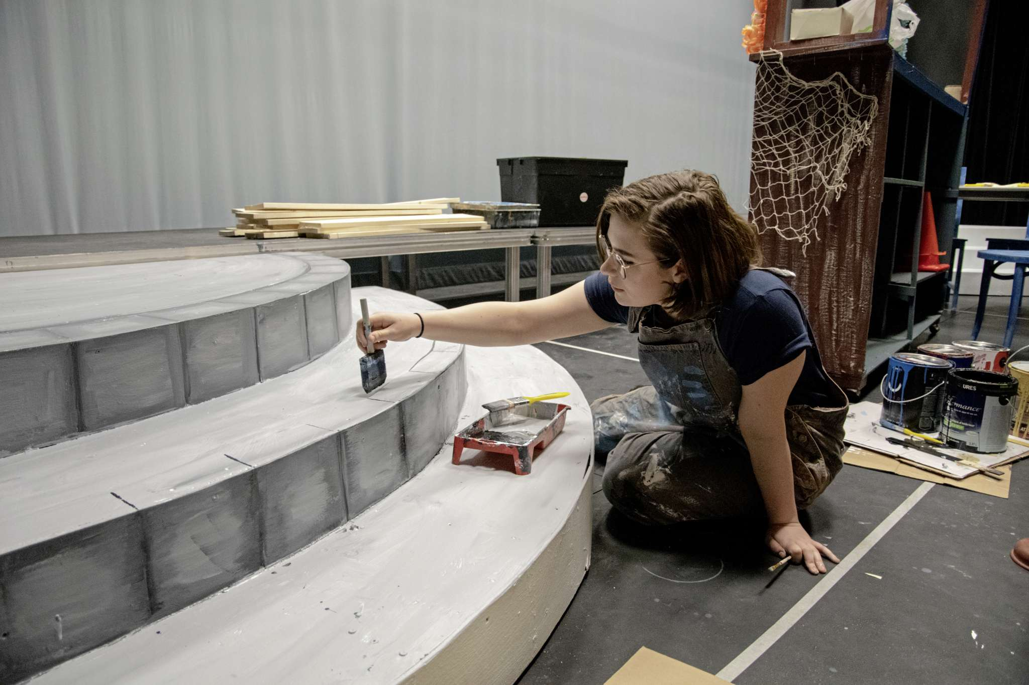 Mamma Mia! crew member Ezri Smith works on a piece of the set for the show.