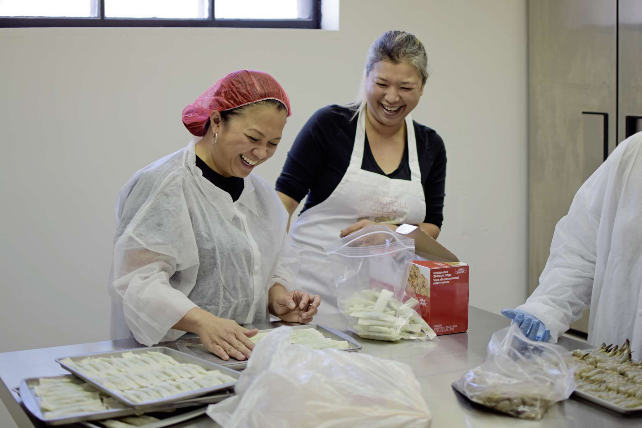 Springroll Queen owner Roweliza Lulu (right) and her friend Heidee Bautista share a laugh while prepping lumpia at the business at 975 Notre Dame Ave.