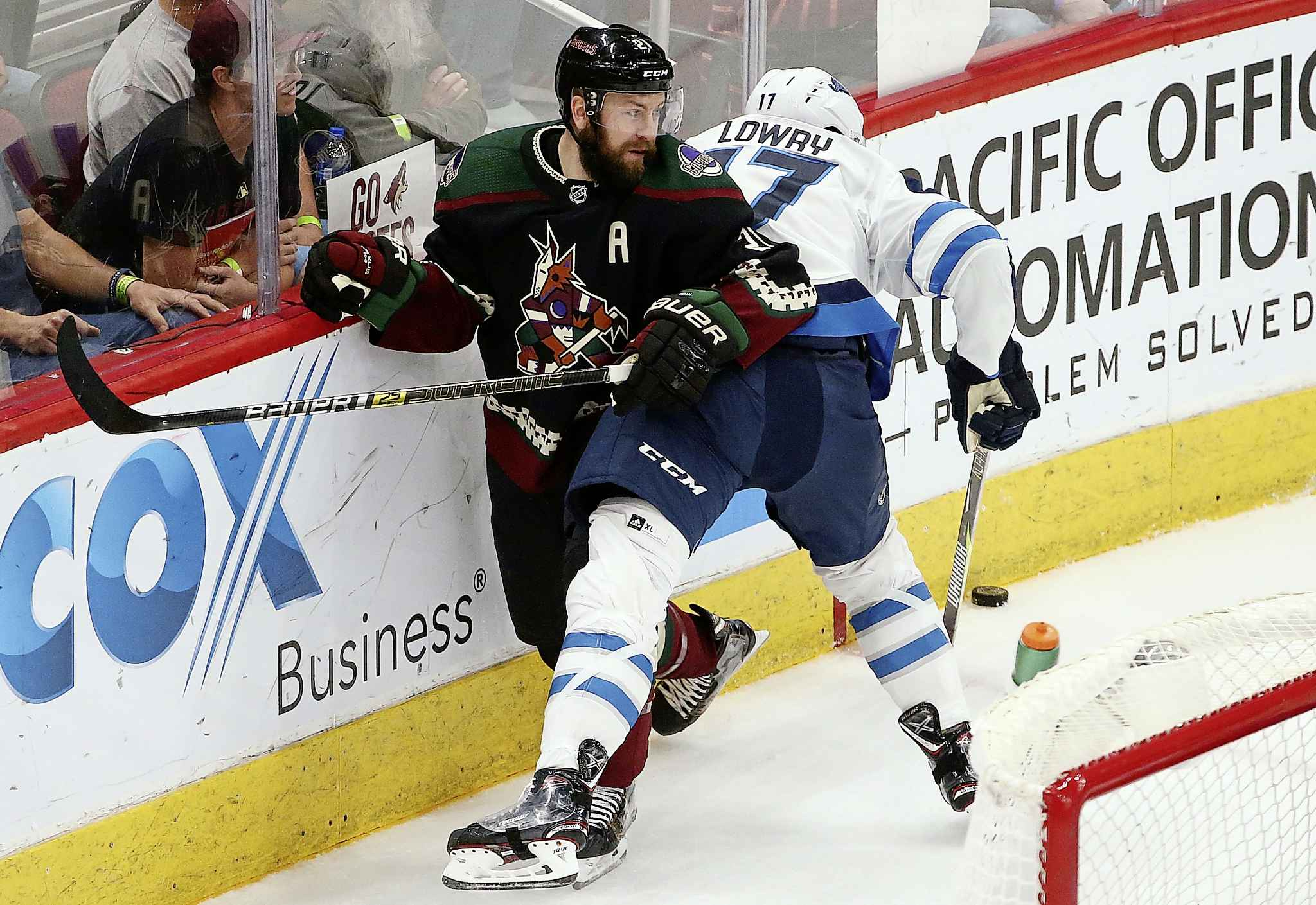 Arizona Coyotes center Derek Stepan (21) tangles with Winnipeg Jets center Adam Lowry, right, as they both go for the puck during the second period of an NHL hockey game Saturday, April 6, 2019, in Glendale, Ariz. (AP Photo/Ross D. Franklin)