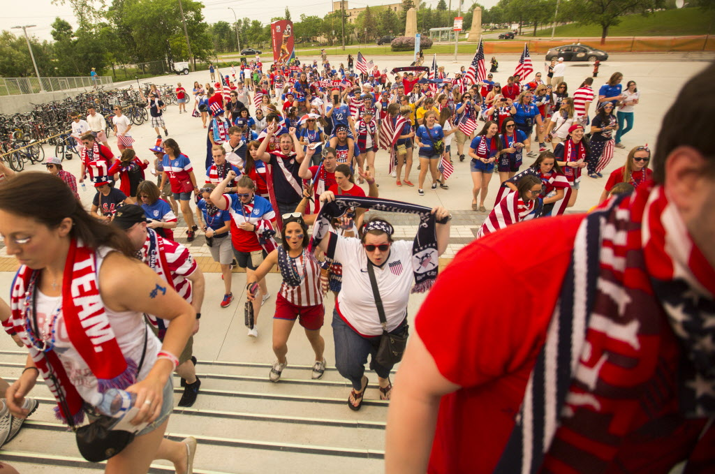 Members of the soccer fan group the American Outlaws march up to the stadium to see the FIFA World Cup United States vs. Australia game at the Investors Group Field Monday. (Mikaela MacKenzie / Winnipeg Free Press)