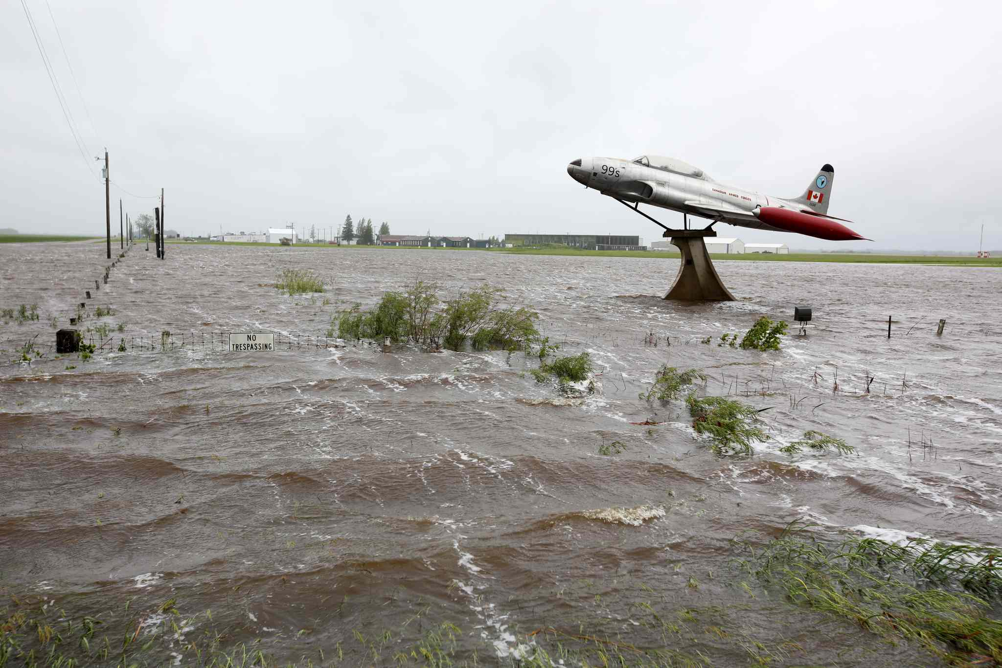Flood waters surround a T33 fighter jet on display along Highway 10 and Sandison Road near the Brandon Municipal Airport on Sunday.  Rain fell almost non-stop throughout the weekend, and the airport was closed due to the flooding.