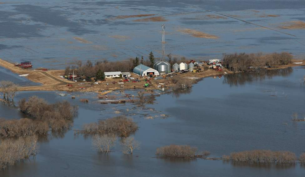 Country roads are washed out by the flooding Morris and Red River near Morris, Manitoba. This farmer outside of the Morris ring dikes has moved all his equipment to higher ground. 