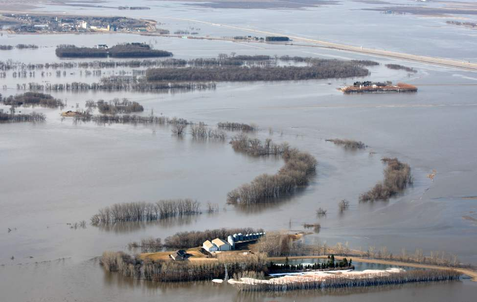 Farmers' properties are surrounded by the flooded Red River north of  of St Jean Baptiste, Manitoba.  The town is located along Highway 75, 40 km north of the United States border. The town of St Jean Baptiste, top, is surrounded by a ring dike keeping it safe from the flood waters.