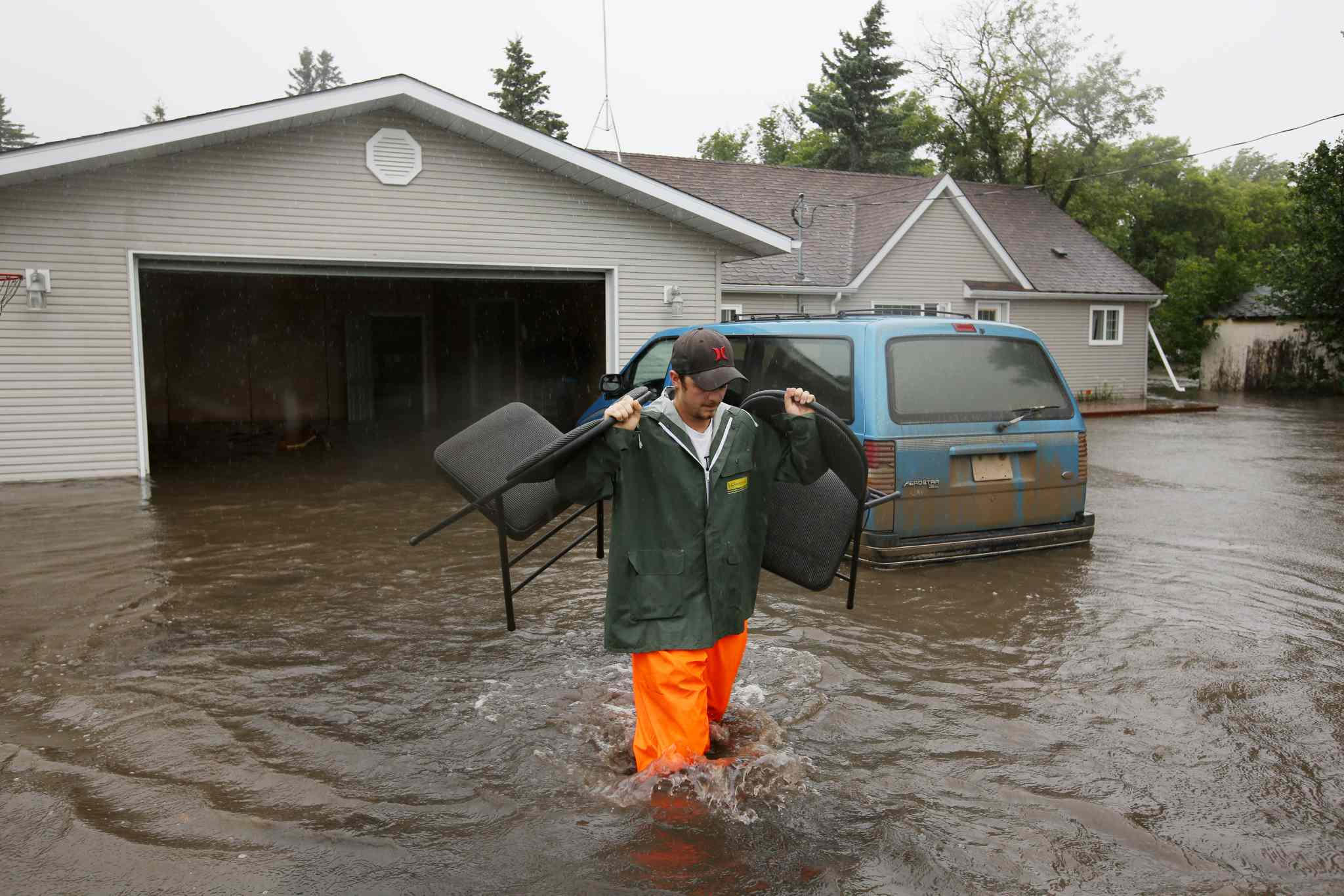 Christian Jeanes carries chairs out of his neighbour's flooded home to a waiting trailer in the village of Cromer in southwestern Manitoba on Sunday. Incessant rainfall over the weekend caused forced the evacuation of approximately 30 residents.