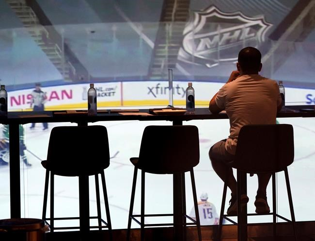 A patron watches TV in a bar prior to NHL exhibition action against the Columbus Blue Jackets in Toronto on Thursday, July 30, 2020. As summer heat shimmers off the pavement and parked cars become stultifying ovens, Canada's favourite winter pastime is officially back. The question is whether fans, finally able to enjoy the outdoors in this COVID year of masks and misery, will tune in to watch NHL playoff hockey beamed in from empty hub-bubble arenas. THE CANADIAN PRESS/Frank Gunn