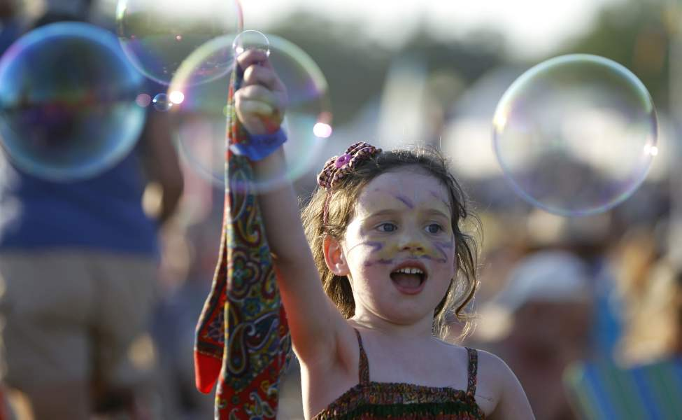 Alice Carey, 5, plays with bubbles while Beth Orton performs at the Winnipeg Folk Festival at Birds Hill Park, Friday. 