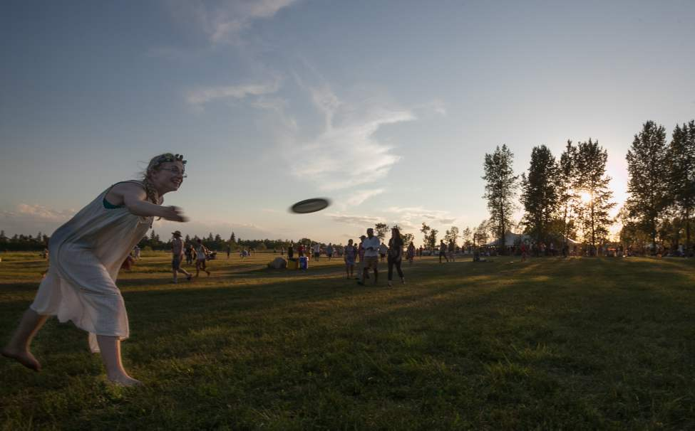 Elise Devoid snags a frisbee just before sunset on Saturday at the 2012 Winnipeg Folk Festival. Melissa Tait / Winnipeg Free Press
