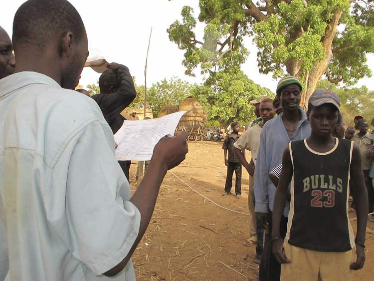 Men line up at a food-distribution centre in western Niger as officials check their names against a list of qualified recipients.