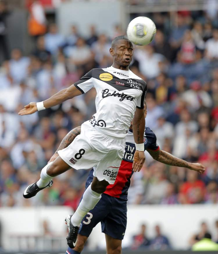 Guigamp's Claudio Beauvue outleaps Gregory Van Der Wiel of Paris Saint Germain during PSG's victory in League One soccer in Paris, Saturday. (Christophe Ena / The Associated Press)