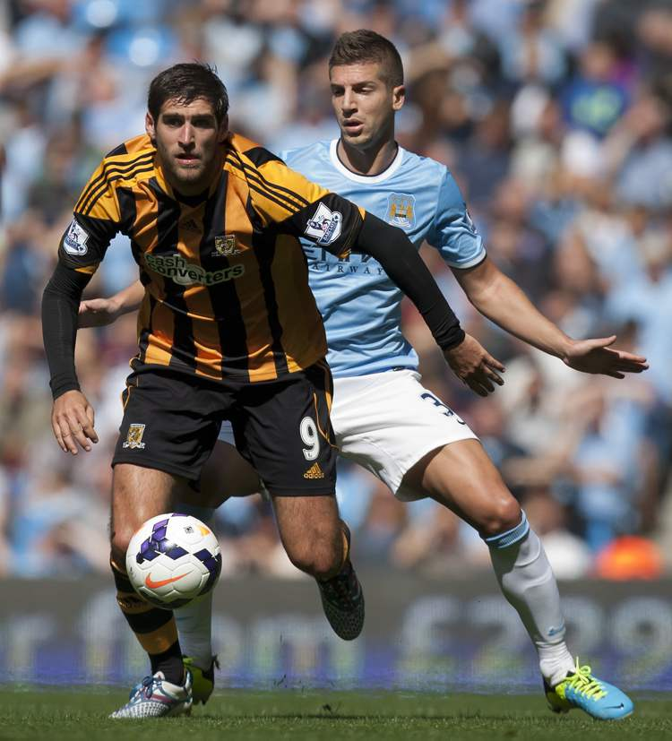 Manchester City's Matija Nastasic (back) chases Hull City Tigers' Danny Graham, during their English Premier League soccer match in Manchester, Saturday. Man City won the game 2-0.  (Jon Super / The Associated Press)