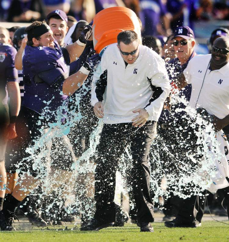 Northwestern coach Pat Fitzgerald is doused in the closing minute of the Wildcats 34-20 victory over Mississippi State in the Gator Bowl NCAA college football game, Tuesday in Jacksonville, Fla.