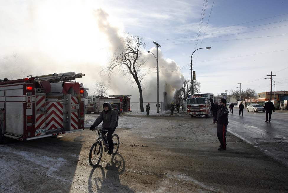 Life goes on as a cyclist rides through an active fire scene on Main Street at Burrows Avenue. Firefighters were met with heavy smoke and flame  when they arrived. No one was injured. February 12 2013 