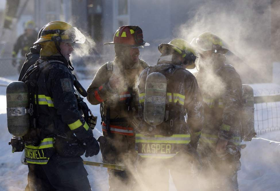 Steam pours off firefighters covered with ice from fighting a winter house fire on Trent Avenue. 