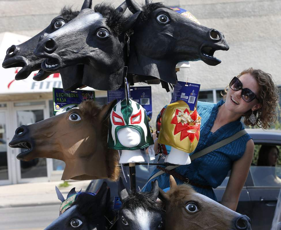 Kristen Adair looks over a collection of horse masks at Gags Unlimited  on Osborne Street during a sidewalk sale. August 23 2013 (KEN GIGLIOTTI / WINNIPEG FREE PRESS)