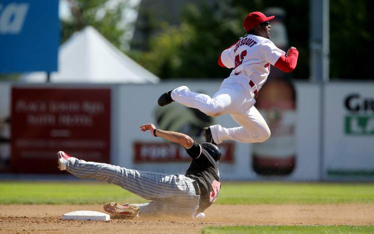 Kevin Moesquit jumps over the slide of Fargo-Moorhead Redhawks Jeremiah Piepkorn in a game earlier this month.