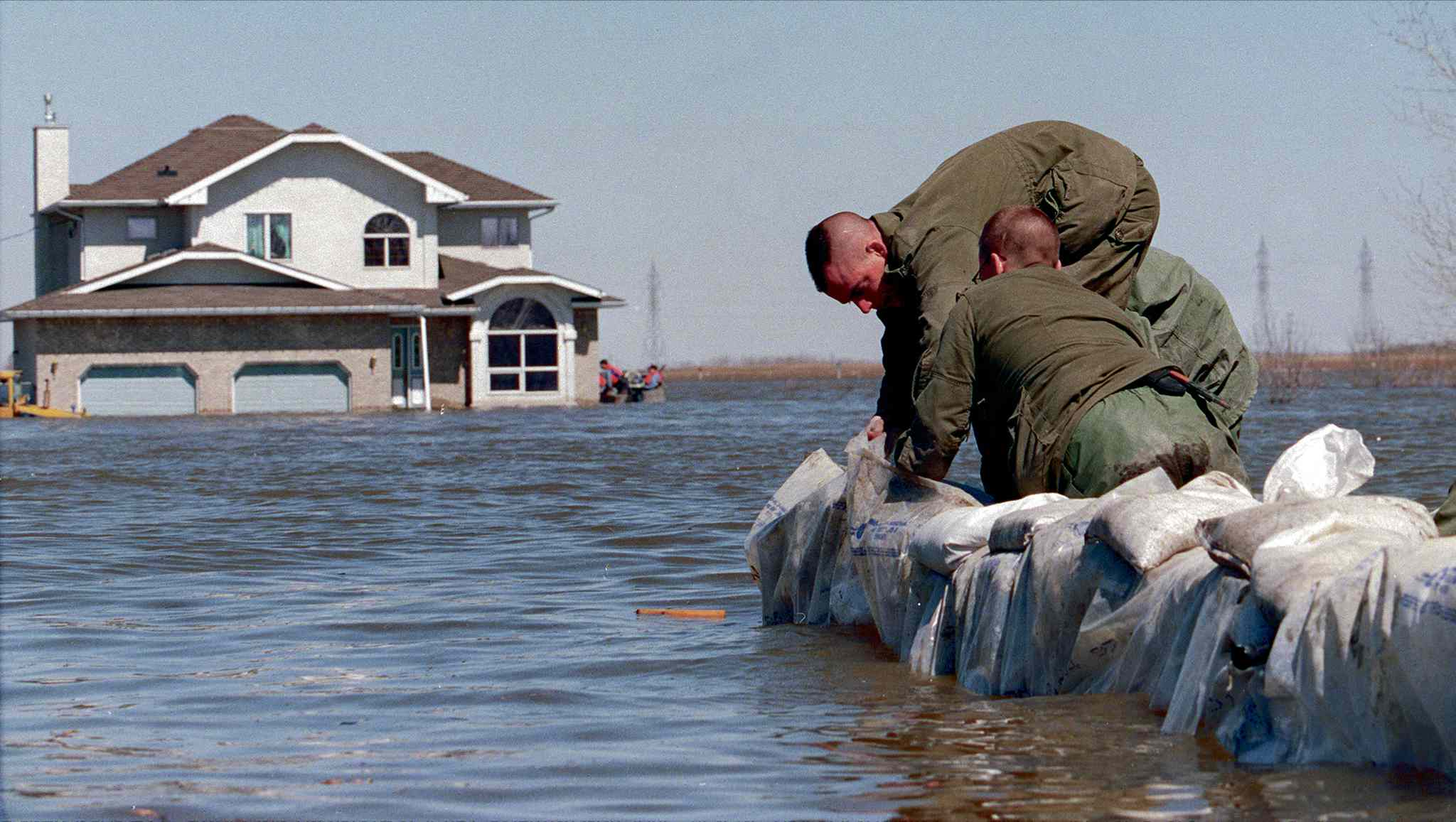 Canadian Forces soldiers help a homeowner build a sandbag dike in Grand Pointe.