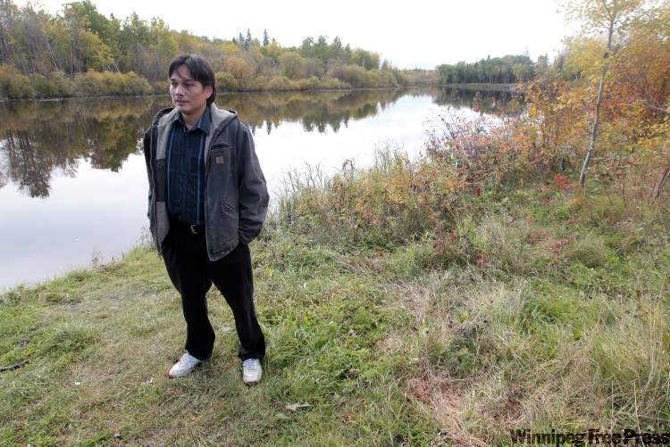 Coun. Denelle Bushie stands by the Wanipigow River, the source for drinking water for Hollow Water First Nation.