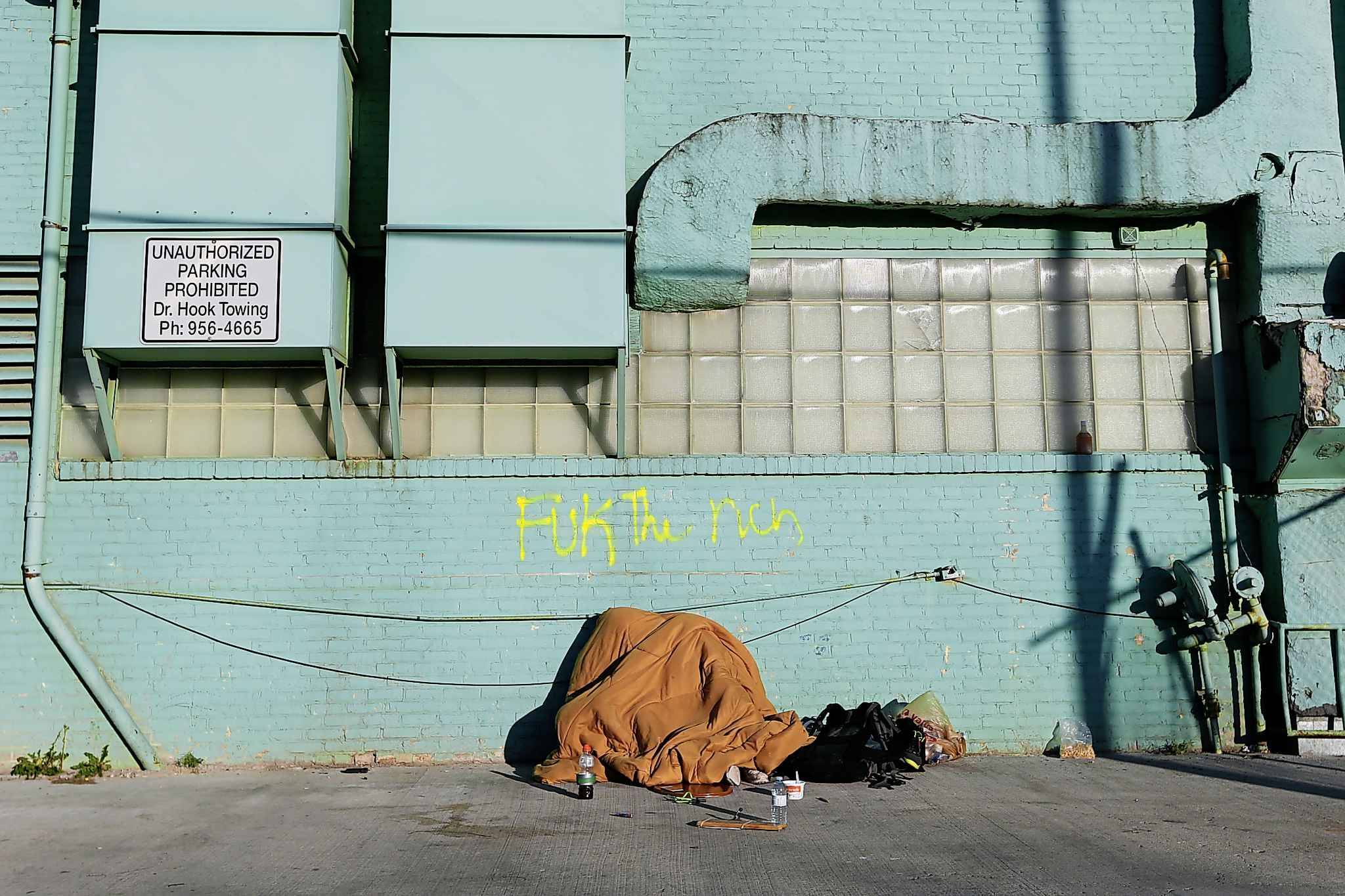 A woman sleeps under a blanket in a backlane in Winnipeg. The shelters are often little more than propped-up tarps providing minimal protection from the elements.