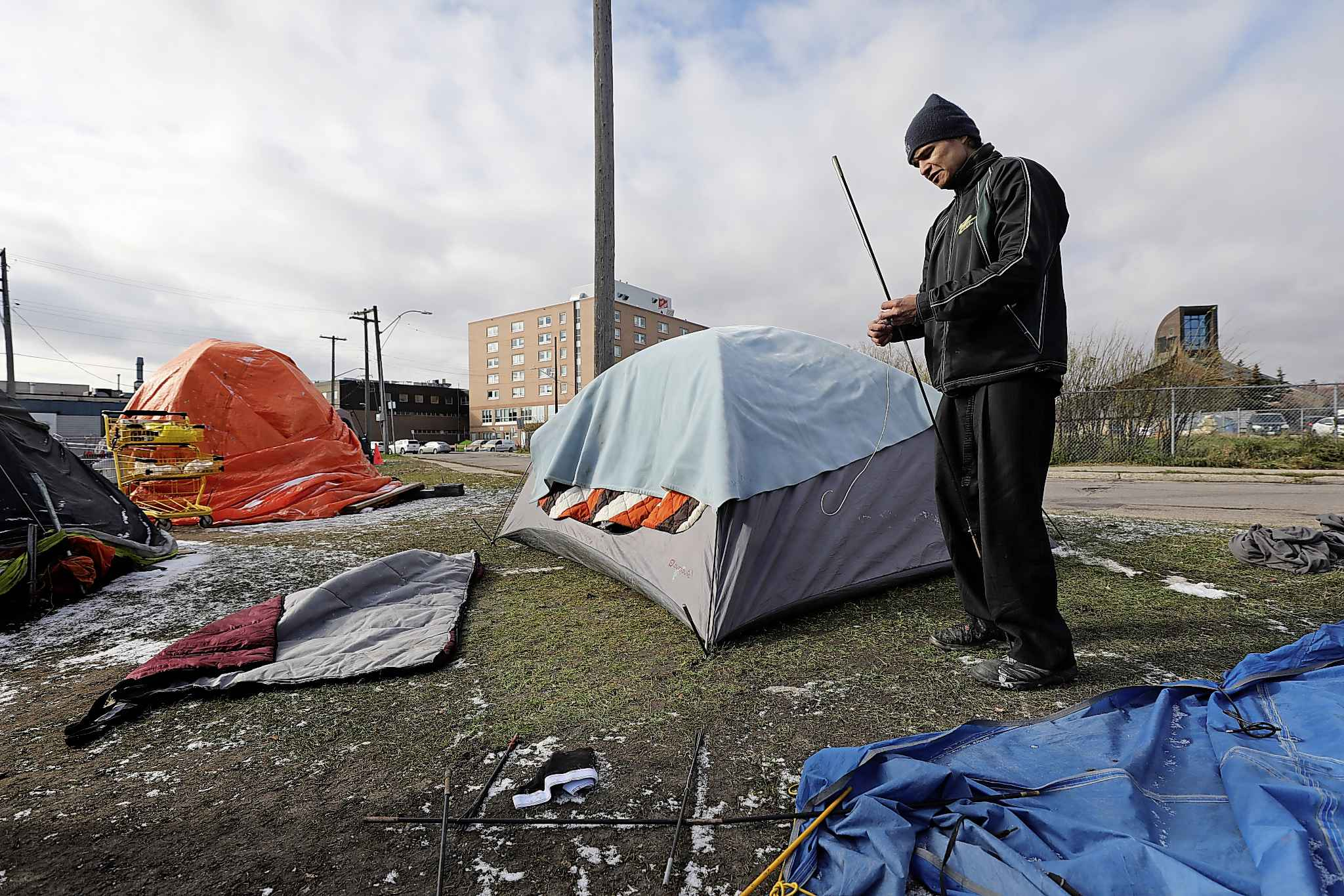Johnny Guiboche, who has been homeless for many years, works on a tent that belongs to his god child near Thunderbird House, Monday.