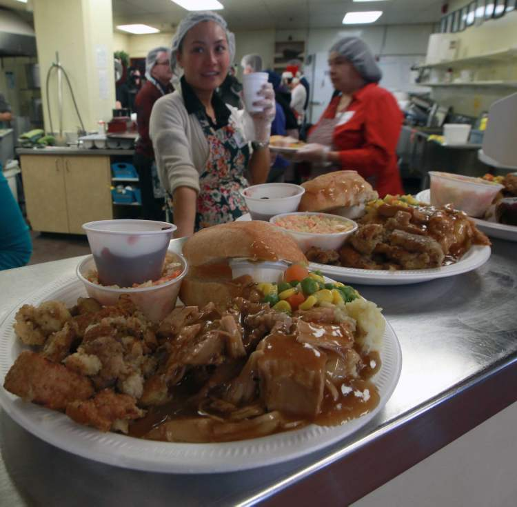 Volunteers prepare a Christmas lunch at Siloam Mission. Between 500 and 700 people were given a turkey dinner with all the trimmings Monday afternoon at the downtown shelter. (Joe Bryksa / Winnipeg Free Press)