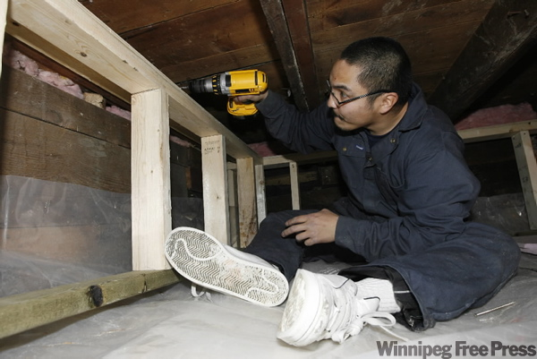 Chris Courchene screws in a frame to insulate a basement in an Aberdeen Avenue home Tuesday.