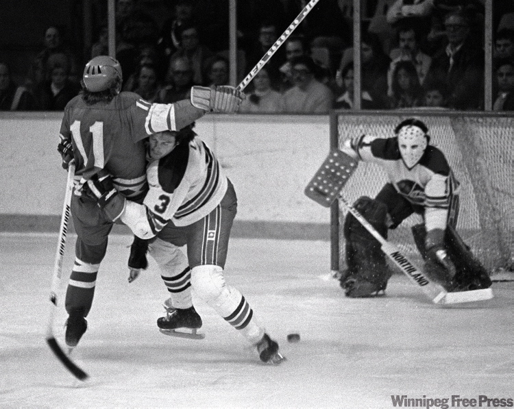 Jets defenseman Barry Long takes out Soviet Red Army player in front of goalie Joe Daley on Dec. 12, 1977.