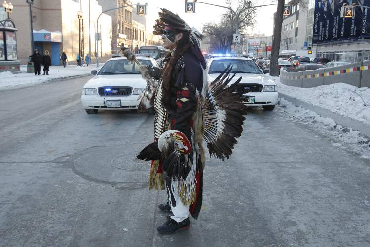 A protester in traditional First Nations costume takes part in the Idle No More protest at Portage and Main.