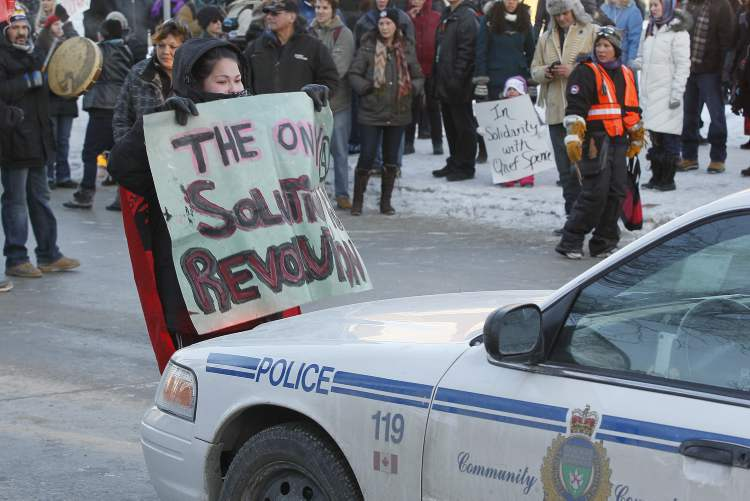 A protester tries to get a message across to police stopping traffic at Portage and Main. (Winnipeg Free Press)