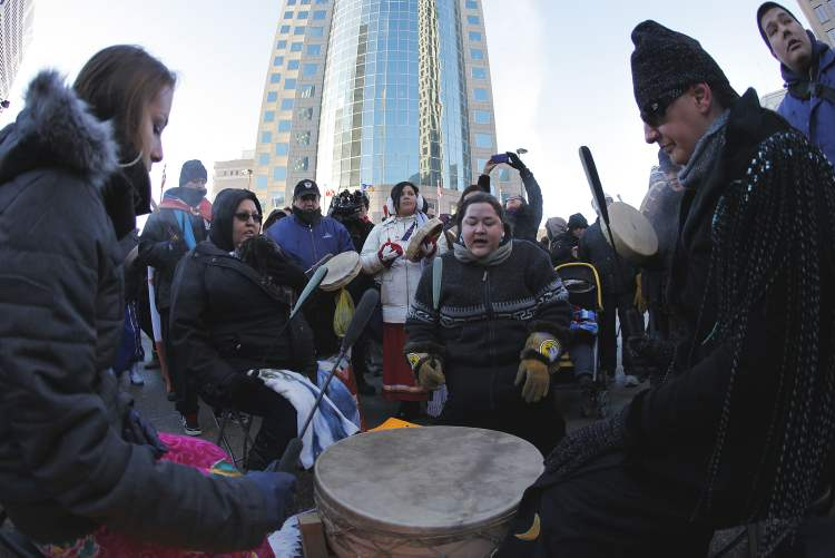 Traditional drums beat at the intersection of Portage and Main. (Winnipeg Free Press)