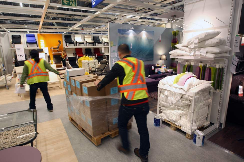 Workers move product as they set up  displays in the new Ikea Winnipeg Wednesday. (JOE BRYKSA / WINNIPEG FREE PRESS)