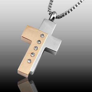 The necklace, a cremation pendant, is a gold and silver cross with five crystals and hangs on a silver chain.