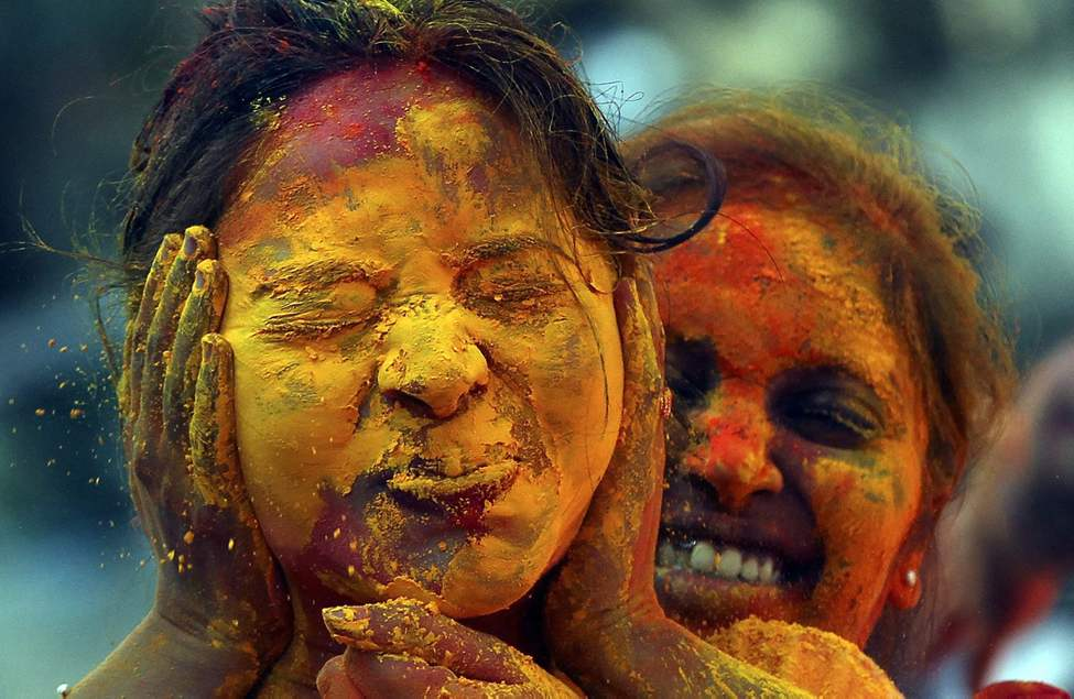A woman reacts as her face is smeared with colored powder during Holi festivities in Mumbai, India, Thursday, March 8, 2012. Holi, the Hindu festival of colors, also heralds the coming of spring. (AP Photo/ Rajanish Kakade) (CP)
